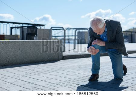 Wasted promenade of ill man. Elderly disappointed charismatic man touching aching knee while demonstrating negative emotions and worrying about his health