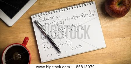Equations over black background against overhead of notepad and pen