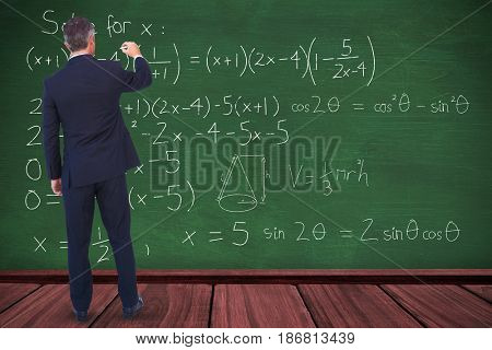 Businessman writing with chalk on white background against green room