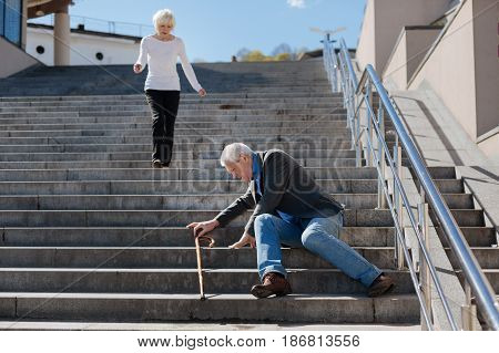 Depressing pain of pensioners. Old trendy fearful man transferring pain in the body and standing up while polite woman going downstairs to him
