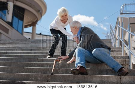 Do not leave anyone in need. White-haired frustrated concerned pensioner sitting in the street and having dizzy while not indifferent woman helping him