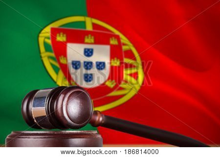 Hammer and gavel against 3d digitally generated portugese national flag