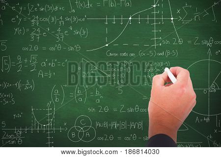 Business man writing with chalk against green background