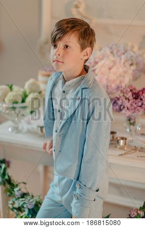 the little boy in the blue suit in the Studio with flowers and candle