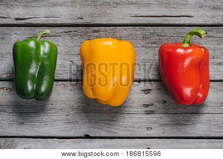 Top View Of Colorful Bell Peppers Laying On Wooden Table, Bell Peppers