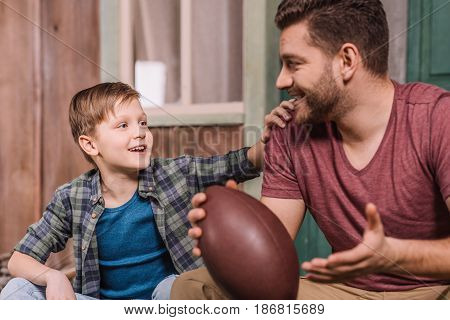 Young Father With Little Son Sitting On Porch At Backyard, Dad And Son Playing