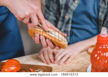 Close-up Partial View Of Little Boy And Father Cutting Bun For Hot Dog, Dad And Son Cooking Concept