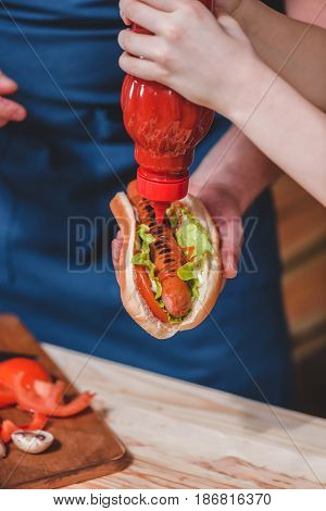 Close-up Partial View Of Father And Son With Ketchup Preparing Hot Dog, Dad And Son Cooking Concept