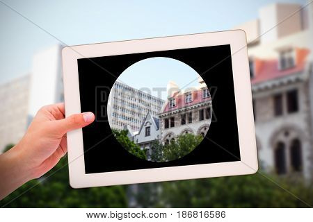 Masculine hand holding tablet against low angle view of city buildings on sunny day