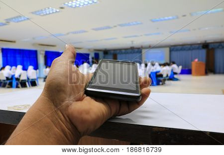 smartphone hand holding in seminar conference classroom: Select focus with shallow depth of field.