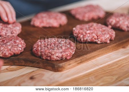 Close Up View Of Raw Meat Patties For Burgers On Wooden Cutting Board