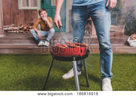 Partial View Of Father Cooking Hot Dog Sausages With Son Behind