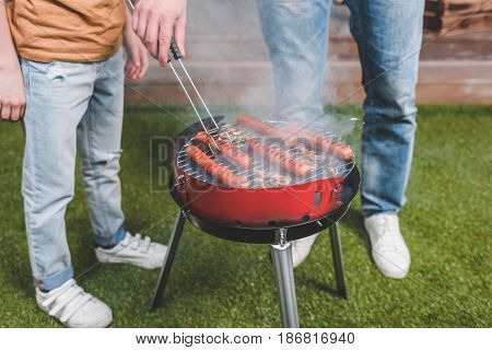 Partial View Of Father And Son Cooking Hot Dog Sausages On Barbecue