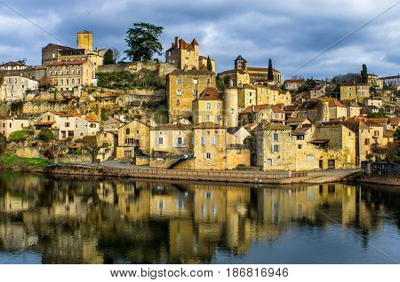 Colorful photograph of the lovely medieval village of Puy l'evêque, in Lot, France