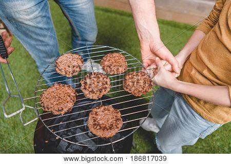 Partial View Of Father And Son Cooking Beef Burgers On Barbecue