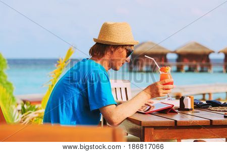 youg man drinking cocktail looking at touch pad on tropical beach resort