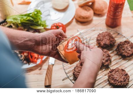 Partial View Of Man Cooking Homemade Burger