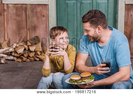 Portrait Of Happy Father And Son Eating Homemade Burgers