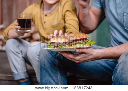 Partial View Of Father And Son Holding Plate With Homemade Burgers