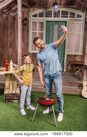 Smiling Father And Son Taking Selfie While Cooking Meat Patties