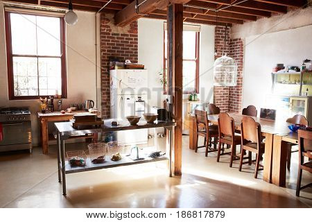 Serving table and dining area in open plan loft apartment