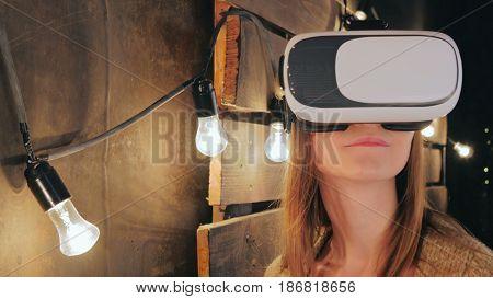 Young woman using Virtual Reality Glasses. Virtual reality mask. VR. Retro loft Christmas background with light bulbs. Close up shot