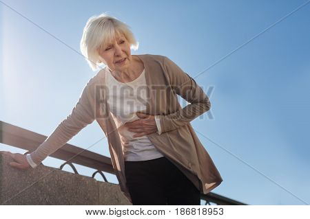 It can happen everywhere. Aged ill scared woman standing and feeling terrible pain in her stomach while walking on the quay