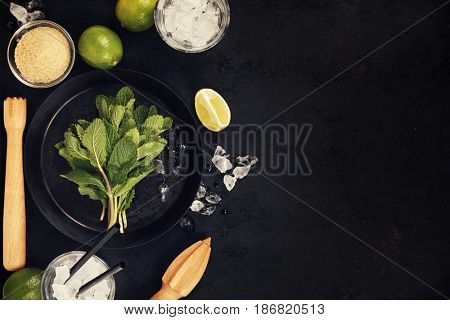 Mojito cocktail ingredients (fresh mint, lime, ice) on rustick background
