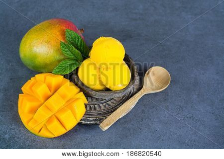 Mango ice cream sorbet with mint leaves and mango fruit in black stone bowl