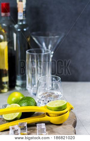 Lime manual press for preparation of cocktails limes and glass with ice cubes party time