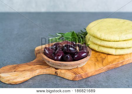 Mediterranean appetizer antipasti tapas calamara olives and garlic pita bread herbs on wooden plank made from olive tree and grey background