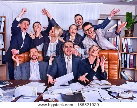 Business people office life of team people are happy with hand up sitting table . Cabinets with folders in background. People in suits glad with successful deal and celebrate success in office.