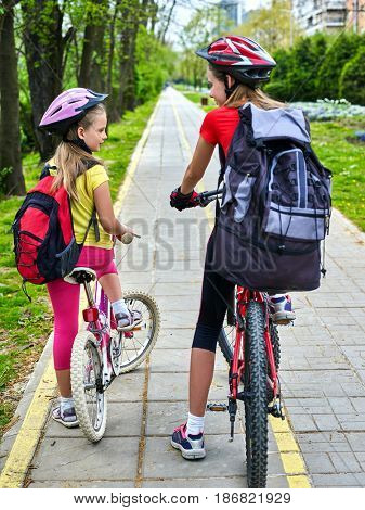 Bicycle path and sign with children. Girls wearing bicycle helmet with rucksack ciclyng ride. Kids are on yellow bike lane. Alternative to urban transport for participate in cycling competitions.