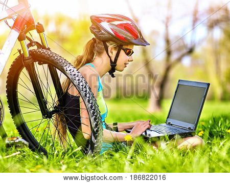 Woman traveling bicycle in summer park. Bicyclist girl watch on laptop. Girl counts pulse after sport training and is looking for way to navigator. Dependence on social networks.