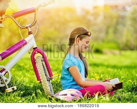Bikes cycling kid girl. Child girl rides bicycle. Girl in cycling reading book near bicycle into park outdoor. Cyclist looking at book. Schoolgirl does homework in nature.