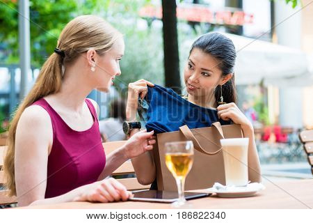 Asian fashionable young woman showing to her best friend a new trendy purchase while sitting down at a trendy cafeteria downtown