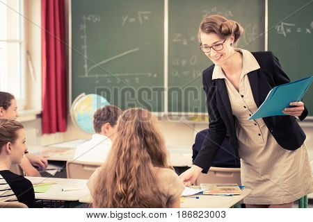 Teacher  handing out class work to her students