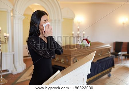 burial, people, grief and mourning concept - close up of sad woman with napkin crying near coffin at funeral in church