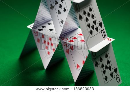 casino, gambling, games of chance, hazard and insecurity concept - close up of house of playing cards on green table cloth
