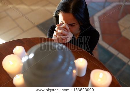 people and mourning concept - sad woman with cinerary urn and candles praying at funeral in church