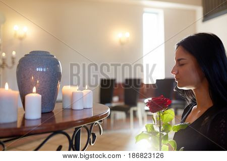 people and mourning concept - sad woman with red rose and cinerary urn at funeral in church
