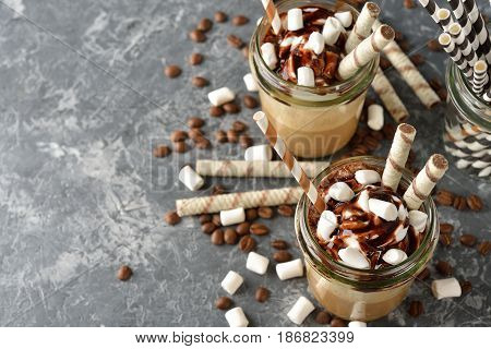 Cold frappe coffee with cream on a gray background