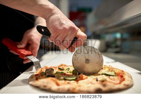 food, italian kitchen and cooking concept - cook with cutter cutting pizza to pieces at pizzeria