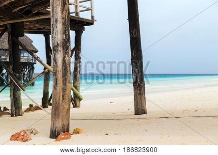 travel, tourism, vacation and summer holidays concept - bungalows or stilt houses on tropical resort beach