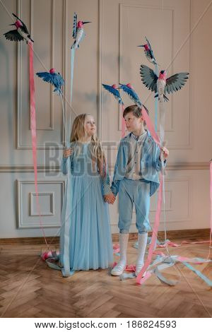 in the Studio the boy in the blue suit and the girl in the blue dress with birds and colored ribbons