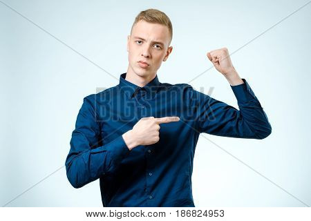 Young Handsome Guy Pointing At His Biceps