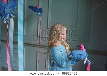 blond girl in a blue dress holding a colored ribbon with birds