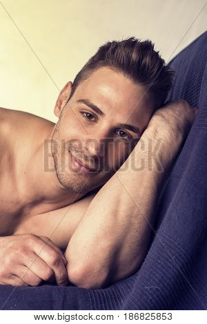 Cute, happy expression, naked young smiling man on blue sheets looking at camera, resting on his arm