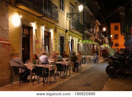 Night view of the narrow streets of Lisbon with cafe outdoors Portugal