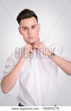 Portrait of a handsome young man in white shirt wearing a wristwatch. Men's beauty, fashion. Businessman. Copy space.